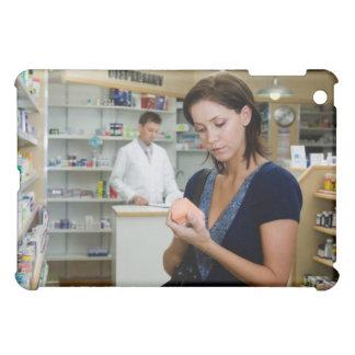Mujer joven que mira la medicina en farmacia,