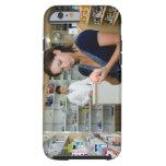 Mujer joven que mira la medicina en farmacia, funda para iPhone 6 tough
