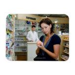 Mujer joven que mira la medicina en farmacia, imán rectangular