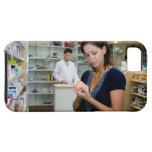 Mujer joven que mira la medicina en farmacia, iPhone 5 fundas