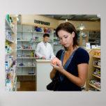 Mujer joven que mira la medicina en farmacia, impresiones