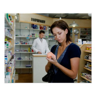 Mujer joven que mira la medicina en farmacia, póster