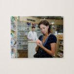 Mujer joven que mira la medicina en farmacia, rompecabezas con fotos