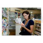 Mujer joven que mira la medicina en farmacia, felicitacion