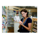 Mujer joven que mira la medicina en farmacia, postales