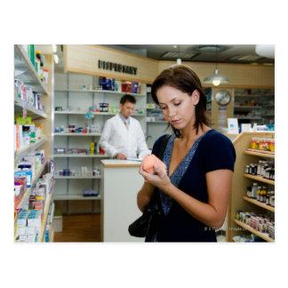 Mujer joven que mira la medicina en farmacia, tarjeta postal