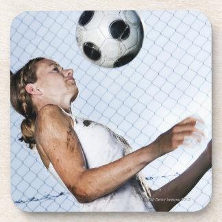 mujer joven que practica con fútbol posavaso