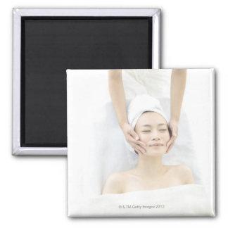 mujer joven que recibe el masaje, mujer en salud imán cuadrado