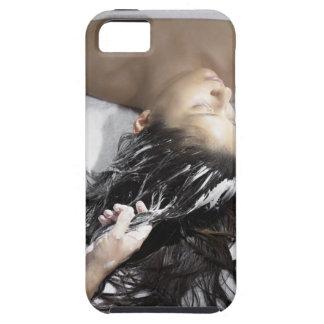 Mujer joven que recibe el tratamiento del pelo iPhone 5 fundas