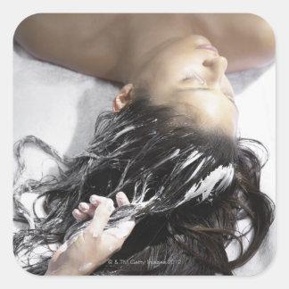 Mujer joven que recibe el tratamiento del pelo pegatinas cuadradases personalizadas