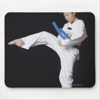 Mujer joven que se realiza alrededor de retroceso mouse pads