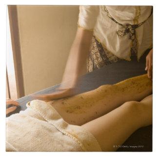 Mujer joven que tiene masaje de la pierna azulejo cuadrado grande
