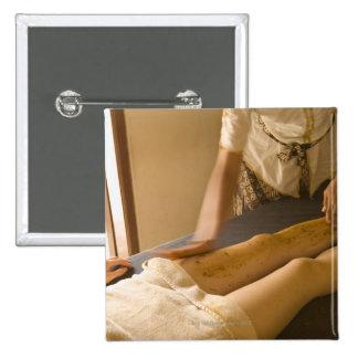 Mujer joven que tiene masaje de la pierna pin cuadrado