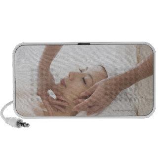 Mujer joven que tiene masaje facial portátil altavoz