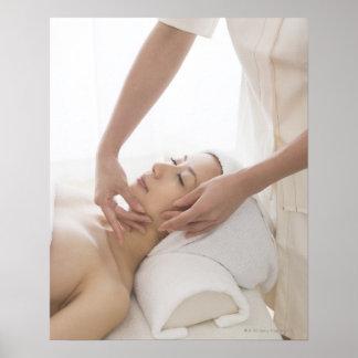 Mujer joven que tiene masaje facial impresiones