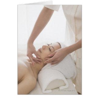 Mujer joven que tiene masaje facial tarjeta de felicitación