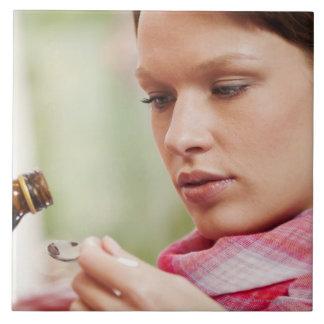 Mujer joven que toma la medicina de la tos azulejo cuadrado grande