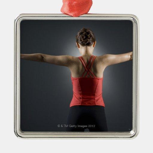 Mujer joven que usa las pesas de gimnasia, vista adorno navideño cuadrado de metal