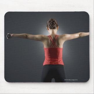 Mujer joven que usa las pesas de gimnasia, vista p tapete de ratones