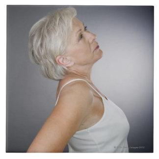 Mujer mayor con dolor de espalda azulejo cuadrado grande