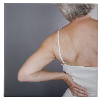 Mujer mayor con el dolor de espalda 2 azulejo cuadrado grande