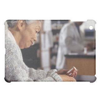 Mujer mayor en botella de la medicina de la lectur