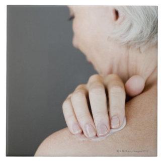 Mujer mayor que aplica la crema hidratante a ella azulejo cuadrado grande