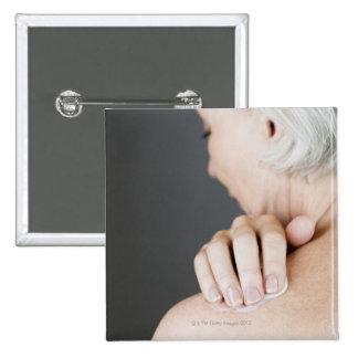 Mujer mayor que aplica la crema hidratante a ella pin cuadrado