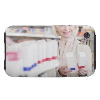 Mujer mayor que compara los paquetes en farmacia carcasa resistente para iPhone