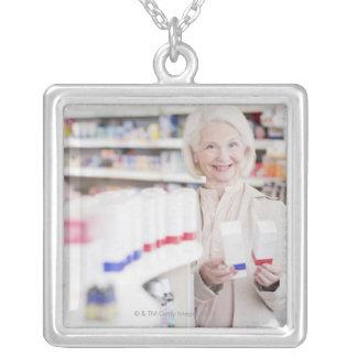 Mujer mayor que compara los paquetes en farmacia colgantes personalizados