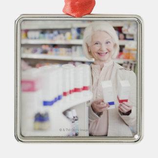 Mujer mayor que compara los paquetes en farmacia ornamentos de navidad