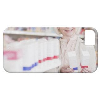 Mujer mayor que compara los paquetes en farmacia funda para iPhone SE/5/5s