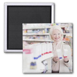 Mujer mayor que compara los paquetes en farmacia imán cuadrado