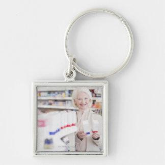 Mujer mayor que compara los paquetes en farmacia llavero cuadrado plateado