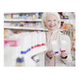 Mujer mayor que compara los paquetes en farmacia postales