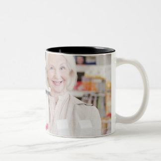 Mujer mayor que compara los paquetes en farmacia taza de café