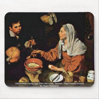 Mujer mayor que fríe los huevos (el viejo cocinero tapete de raton