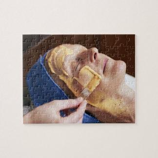Mujer mayor que hace crema facial aplicar puzzle