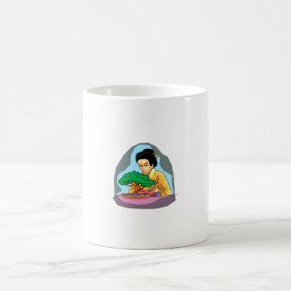 Mujer oriental que tiende bonsais taza básica blanca