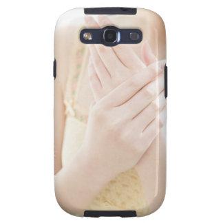 Mujer que aplica la crema del cuidado de la mano samsung galaxy s3 carcasas