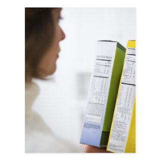 Mujer que compara etiquetas de la nutrición tarjetas postales