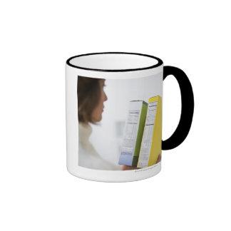 Mujer que compara etiquetas de la nutrición taza de café