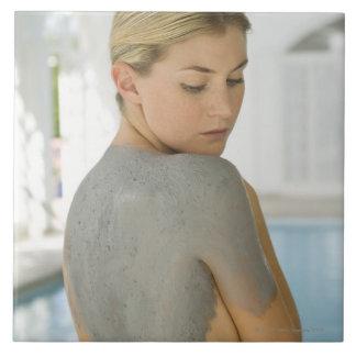 Mujer que consigue el tratamiento de la piel del b azulejo cuadrado grande