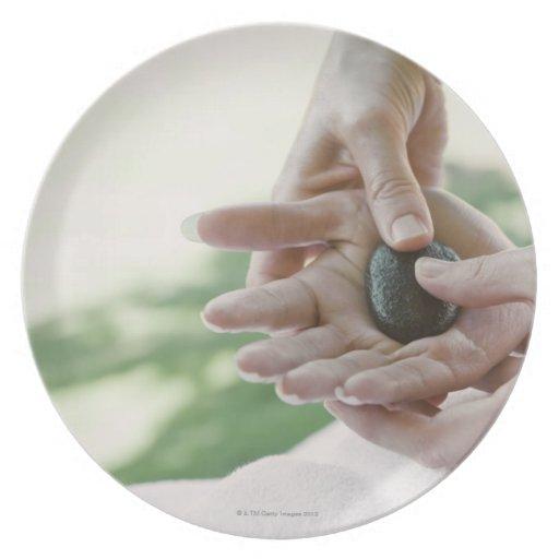 Mujer que consigue masaje de la mano con la piedra plato de cena