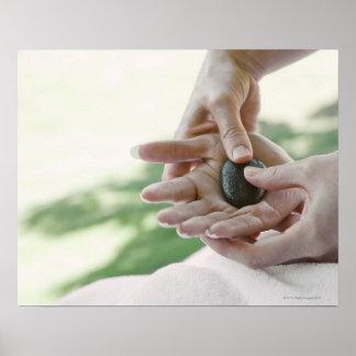 Mujer que consigue masaje de la mano con la piedra póster