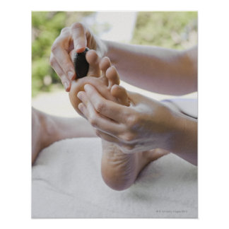 Mujer que consigue masaje del pie con la piedra ca impresiones