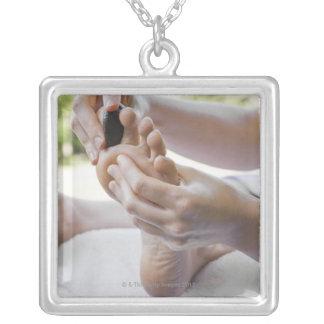 Mujer que consigue masaje del pie con la piedra colgante cuadrado