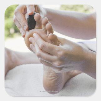 Mujer que consigue masaje del pie con la piedra pegatina cuadrada