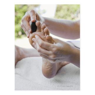 Mujer que consigue masaje del pie con la piedra postal