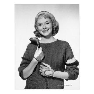 Mujer que detiene al club de golf tarjeta postal